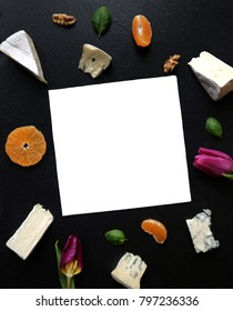 Assorted cheese with fruits and flowers on a black stone background. Blue cheese, brie cheese, Gorgonzola, mandarins, pomegranate, tulips. Space for text, top view.