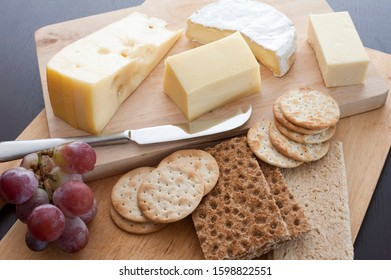Assorted cheese platter served on a buffet as an appetizer with crackers, water biscuits and a small bunch of fresh red grapes