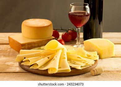 assorted cheese with red wine on a rustic table