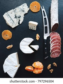 Assorted cheese and white salami with mandarin and nuts. Knife for cheese, black stone background. Gorgonzola, Brie, Roquefort cheese board. Top view. Gourmet, French cuisine.