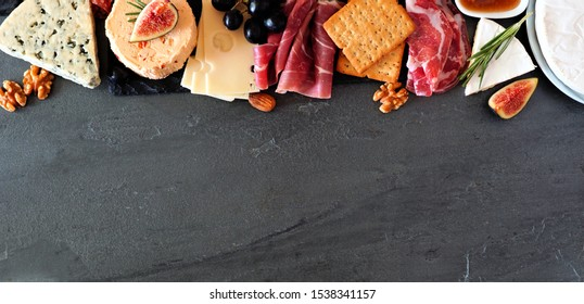 Assorted cheeses and deli meat appetizers. Top border, above view banner on a dark stone background with copy space.