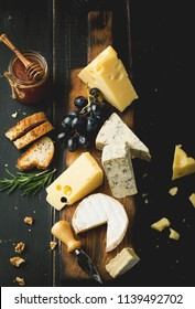Assorted cheeses with grapes, nuts and rosemary on a wooden background