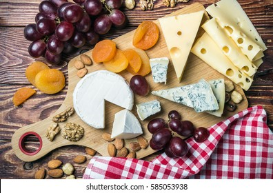 assorted cheeses, nuts and grapes on a wooden table. vignetting as an artistic effect