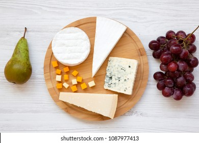 Assorted cheeses on a round board with fruits on a white wooden background. Food for wine, top view. Flat lay. From above.