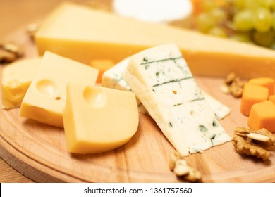 Assorted cheeses on round wooden board plate Camembert cheese, hard cheese slices, walnuts