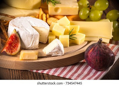 Assorted cheeses on round wooden board plate. Camembert cheese, cheese grated bark of oak, hard cheese slices, walnuts, grapes, crackers, bread, figs