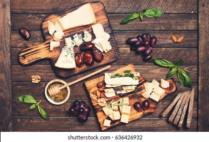 Assorted cheeses on wooden board plates served with nuts, grapes, bread, honey, and dates on dark wood background, top view.