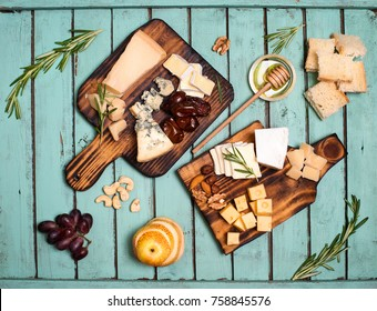 Assorted cheeses on wooden board plates served with nuts, grapes, bread, honey, and dates on shabby chic wood background, top view.