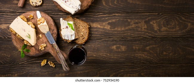 Assorted cheeses on wooden boards plate, bread and wine on dark wooden background, top view, flat lay, copy space, banner.
