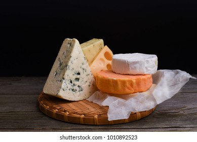 Assorted cheeses on wooden table. Camembert cheese, Roquefort cheese,hard cheese slices, blue cheese, walnuts, grapes, crackers, bread, thyme, dark wood background. Menu design horizontal.