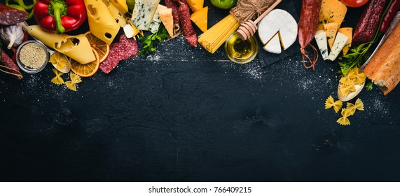 Assorted cheeses, sausages, wines, traditional spices and fresh vegetables on a wooden background. Cheese brie, blue cheese, gorgonzola, fuete, salami. Italian and Spanish Cuisine. Free space.