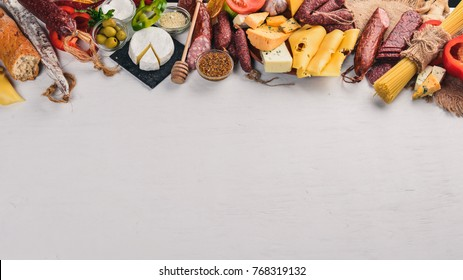 Assorted cheeses and traditional sausages and vegetables on a white wooden background. Cheese brie, blue cheese, gorgonzola, fuete, salami. Italian Traditional Cuisine. Free space for text. Top view.
