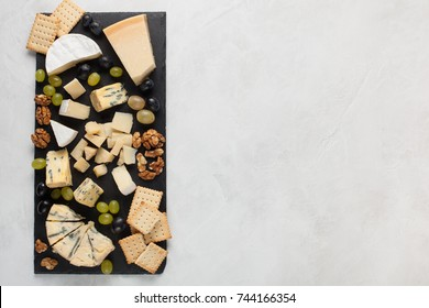 Assorted cheeses with white grapes, walnuts, crackers on a stone Board. Food for a romantic date on a light background. Top view with copy space.
