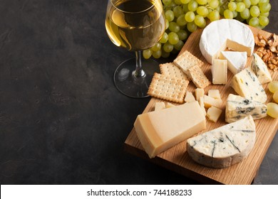 Assorted cheeses with white grapes, walnuts, crackers and white wine on a wooden Board. Food for a romantic date on a dark stone background. Top view with copy space.