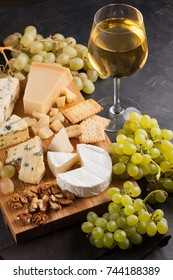 Assorted cheeses with white grapes, walnuts, crackers and white wine on a wooden Board. Food for a romantic date on a dark stone background. Top view.