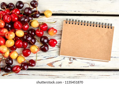 Assorted cherries and closed paper notebook. Heap of ripe sweet berries and binder notepad on vintage wooden background.