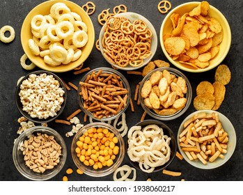 Assorted chips, popcorn, onion rings, croutons, cheese balls, biscuits in bowls. unhealthy food for figure, heart, skin, teeth. An assortment of fast carbohydrates. Junk food on a stone background.