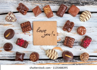 Assorted chocolate candies on wooden background. Set of delicious chocolate candies and Valentines Day card, top view. Sweet gift on holiday.