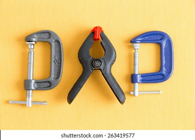 Assorted clamps from Dad's tool kit with adjustable grey and blue G-clamps and a spring loaded plastic A-clamp arranged in a line on a yellow background in a DIY concept