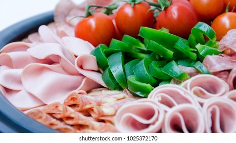 Assorted cold cuts of different sausages with bell pepper and tomatos.
