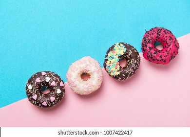 Assorted colored donuts in a row, minimalism on a blue and pink background, top view