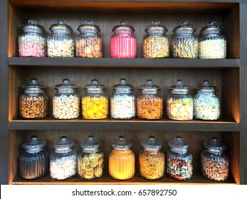 Assorted colorful candies in a glass jar on a wooden shelf. Happy hallow. Differnt color candies.