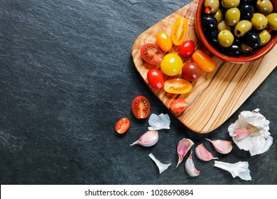 Assorted colorful cherry tomatoes with olives and garlic on slate