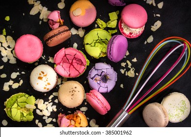 Assorted colorful french macarons and almond flakes with a whisk on a black background. Closeup. Top view. Concept of the baking macarons