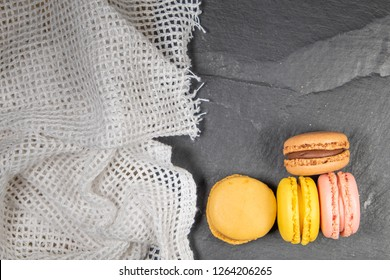 Assorted colorful french macarons isolated on chalkboard stone background with dishcloth. Pastel colors - Image