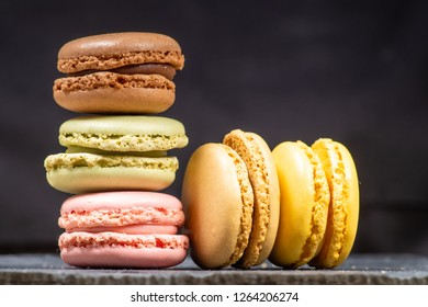 Assorted colorful french macarons isolated on chalkboard stone background. Pastel colors - Image