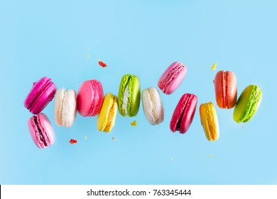 Assorted colorful macaroons falling cookies on blue background