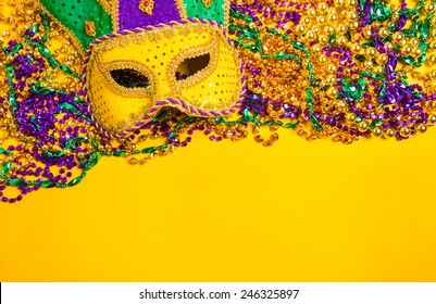 Assorted colorful Mardi Gras mask on yellow background