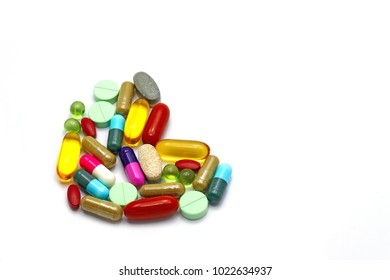 Assorted colorful pharmaceutical medicine pills, tablets and capsules arranged to heart shape isolated on white background with copy space for text. Vitamins herbs supplements health.(selective focus)