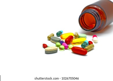 Assorted colorful pharmaceutical medicine pills, tablets and capsules spread messy from glass amber bottle on white background with text  copy space. Vitamins herbs supplements for modern lifestyle.