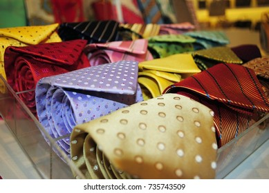 Assorted colorful men's ties rolled up at a store