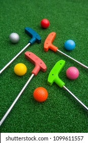 Assorted colors of Mini Golf clubs and balls  on synthetic grass