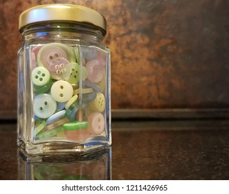 Assorted coloured buttons in a glass jar against a dark background with copy space.