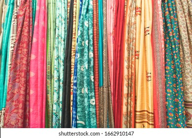 Assorted colourful Indian saris, showcased for retail display. Varieties of fashionable design and ethnic motifs can been seen in each sari.