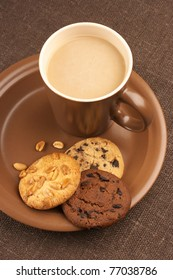 Assorted cookies and brown mug of cappuccino on brown ceramic plate.