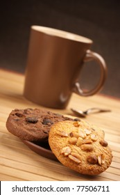Assorted cookies and brown mug of coffee on wooden mat.