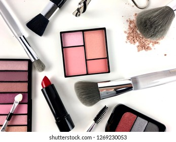 Assorted cosmetics and makeup applicators on white background