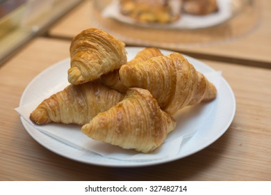 Assorted Croissants on white plate sitting on wood cutting board