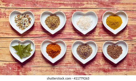 Assorted culinary spices and condiments in heart shaped dishes arranged in two rows on a rustic wood background, overhead view