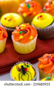 Assorted cupcakes with yellow and orange icing decorated for Autumn.
