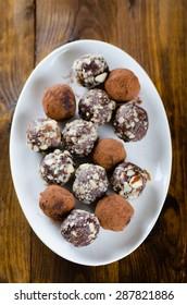 Assorted dark chocolate truffles on a dessert plate on dark wood