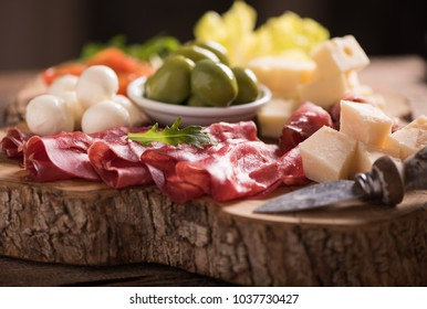 Assorted deli meats and a plate of cheese, on a wooden cutting board. Italian antipasti
