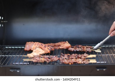 Assorted delicious grilled meat with beef stick and beef steak on black stove with smoke. grills some kind of marinated meat and vegetable on gas grill during summer party time.