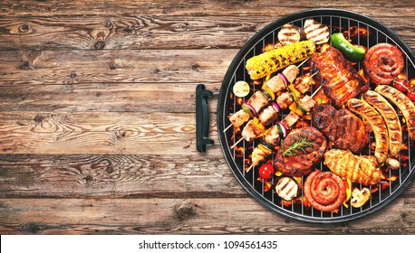 Assorted delicious grilled meat and bratwurst with vegetables over the coals on a barbecue on rustic wooden background