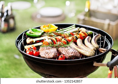 Assorted delicious grilled meat and bratwurst with vegetables over the coals on a barbecue