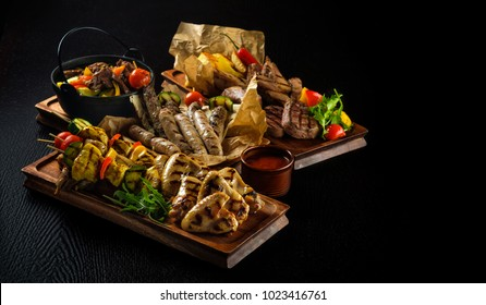 Assorted delicious grilled meat with vegetable. Mixed grilled bbq meat with vegetables. Mixed grilled meat on wooden platter. Copyspace.